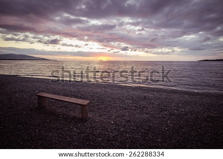 Empty wooden bench placed on pebbly beach with romantic sky at sunset on the coastline of Sulawesi, Indonesia. Concept of loneliness and failure. Marsala toned image, vignetting added. - stock photo