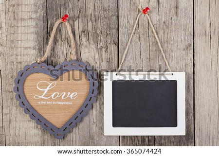 Empty wooden blackboard sign and heart shape frame with love text on wooden background.