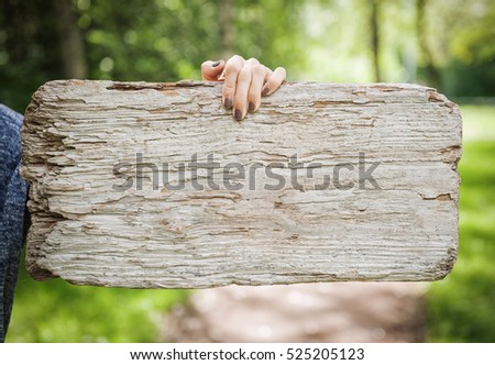Empty wooden board hold by woman hand outdoor. Template mock up