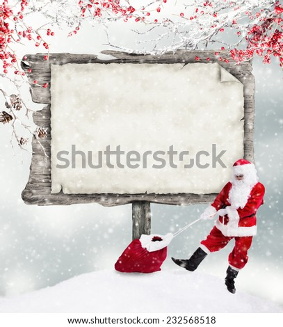Empty wooden board with copy-space for text with Santa Claus and sack of gifts - stock photo