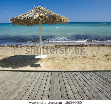 Empty wooden boardwalk with beautiful sandy beach in the background - stock photo