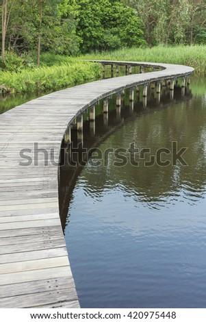 Empty Wooden bridge across in the lake - stock photo