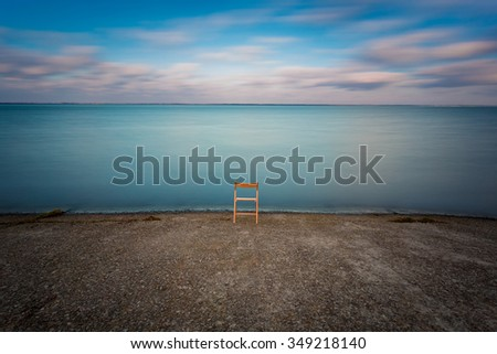 Empty wooden chair on the river embankment. - stock photo