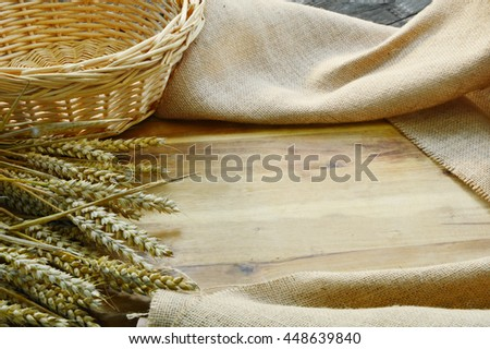 Empty wooden cutting board and basket with wheat,Sackcloth for backgrounds or wallpaper.
