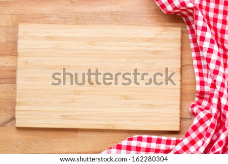 empty wooden cutting board  and cloth red napkin - stock photo