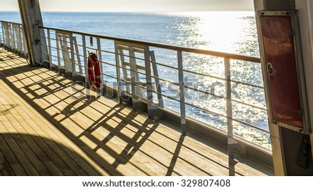 Empty wooden deck and railing with a life ring hanging on the rail on a passenger boat or cruise ship, with sparkling sunshine reflecting on the water of the ocean in a travel concept - stock photo