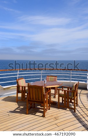 Empty wooden deck chairs and table on ship standing near metal rail. Cruise and sea voyages on summer vacation.