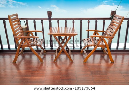 Empty wooden deck chairs and table on ship standing near wooden rail. Blue cloudy sky in background. Comfortable boat tour. Cruise and sea voyages on summer vacation.