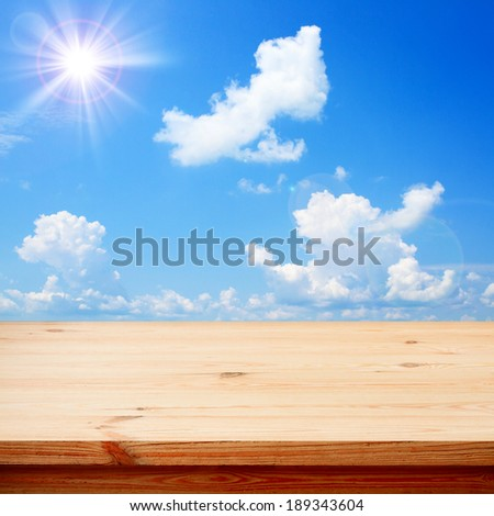 Empty wooden deck table for product montage. Sunny Day, Blue Sky with Clouds Free space for your text  - stock photo