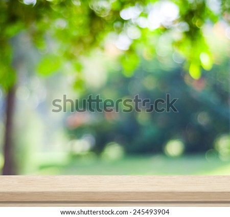 Empty wooden deck table over blurred tree with  bokeh background, for product display montage - stock photo