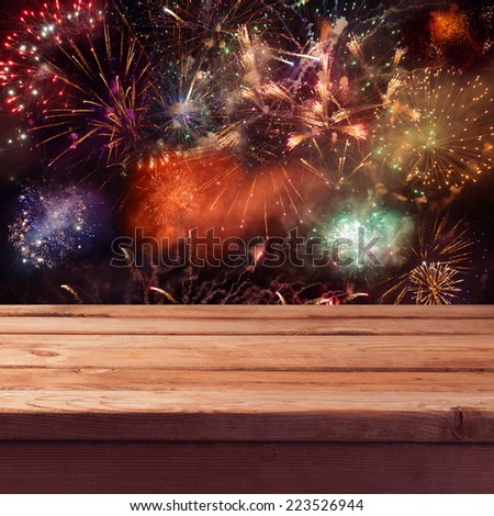 Empty wooden deck table over fireworks background. New Year eve celebration - stock photo