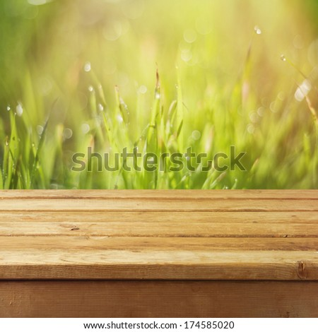 Empty wooden deck table over grass bokeh background. Ready for product montage display - stock photo