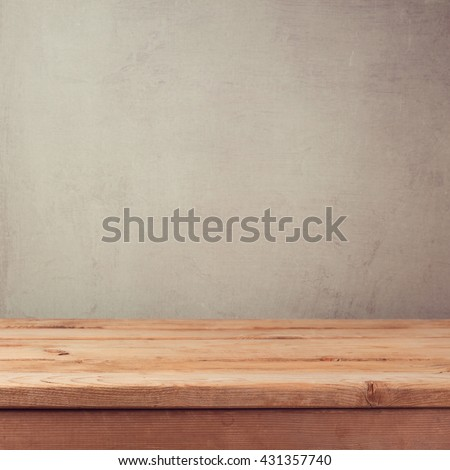 Empty wooden deck table over grey grunge wallpaper - stock photo