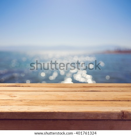 Empty wooden deck table over sea bokeh background. Summer holiday vacation background. - stock photo