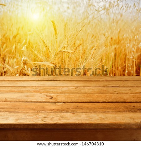 Empty wooden deck table over wheat field with sunset or sunrise. Ready for product montage - stock photo