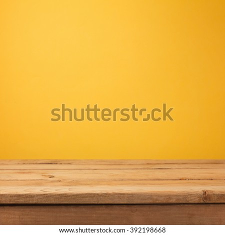 Empty wooden deck table over yellow wallpaper background