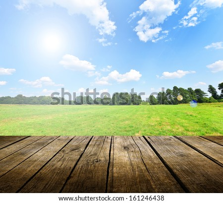 Empty wooden deck table with blue sky in background. Ready for product display montage.  - stock photo