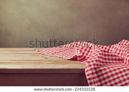Empty wooden deck table with checked tablecloth for product montage display - stock photo