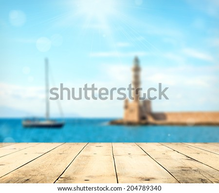 Empty wooden deck table with copyspace and bokeh travel background. - stock photo