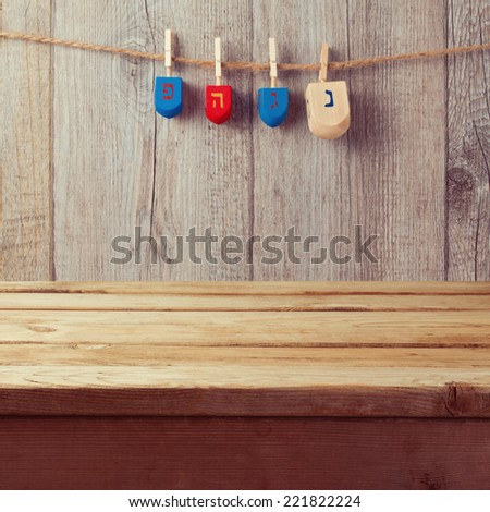 Empty wooden deck table with Hanukkah dreidel spinning top hanging on string - stock photo