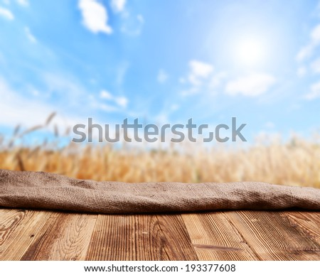 Empty wooden deck table with rye field in background - stock photo