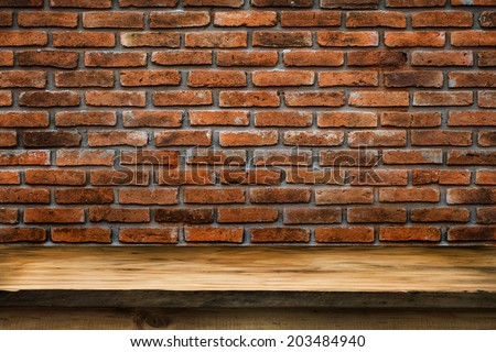 Empty wooden deck table with vintage brick wall pattern. Ready for product display montage. - stock photo