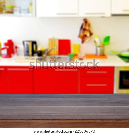Empty wooden desk and defocused modern kitchen for product display montages - stock photo
