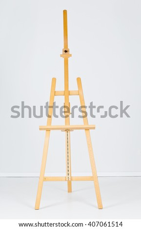 Empty wooden easel in front of white wall - stock photo