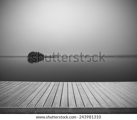 Empty wooden footbridge with calm foggy lake water surface in the background, Mazury, Poland - stock photo