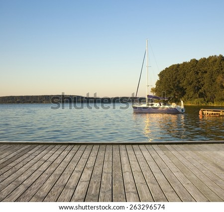 Empty wooden jetty on the lake shore with a yacht moored by a jetty in the background - stock photo