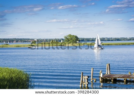 Empty wooden jetty on the lake shore with island and yachts in the background, Mazury, Poland - stock photo