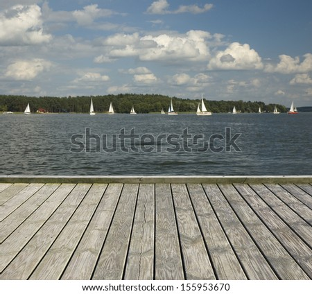 Empty wooden jetty on the lake shore with sailboats in the background