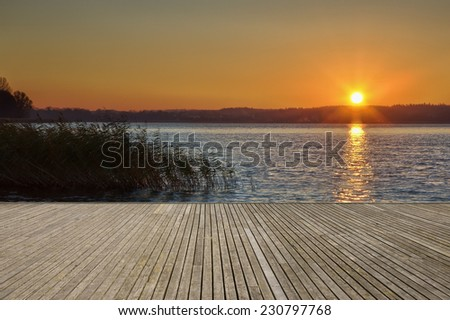 Empty wooden jetty on the lake shore with small island in the background just after sunrise - stock photo