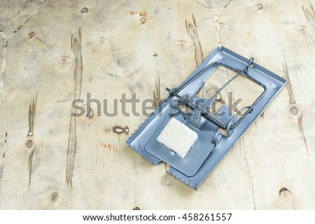 empty wooden mouse trap isolated on wooden background.