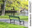 Empty wooden park bench overlooking a lake or pond in the Halifax Public Gardens, Halifax, Nova Scotia, Canada. - stock photo