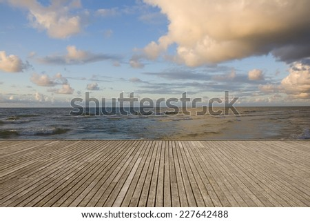 Empty wooden pier with Baltic Sea coast in the background just before sunset - stock photo