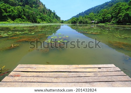 Empty wooden pier with lake in the midst of mountains. - stock photo