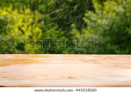Empty wooden plank table against summer rain and bright green defocused foliage. Background for product or object montage template - stock photo