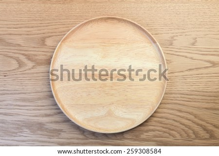 empty wooden plate on wooden table - stock photo