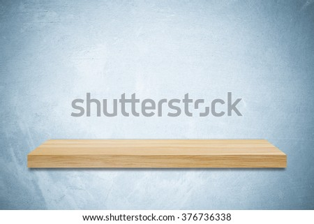 Empty wooden shelf on blue cement wall background, product display montage