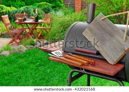 Empty  Wooden Signboard Hanging On Barbecue Grill Appliance, Grilling Tools And Wooden Table With Food And  Beverages On The Backyard Lawn In  Background, Summer Family Home Party Or Picnic Concept - stock photo