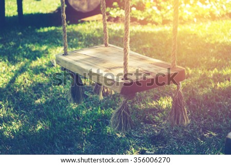 empty wooden swing in children playground with vintage filter - stock photo