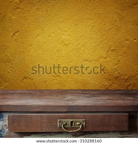 Empty wooden table against a yellow wall. A template, a place for. Background, texture. Grunge texture. - stock photo