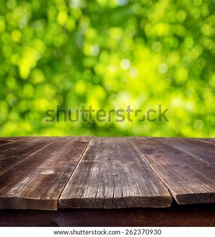 empty wooden table against sunny garden - stock photo