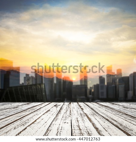 Empty wooden table and Double exposure of blur city and sunset nature background
