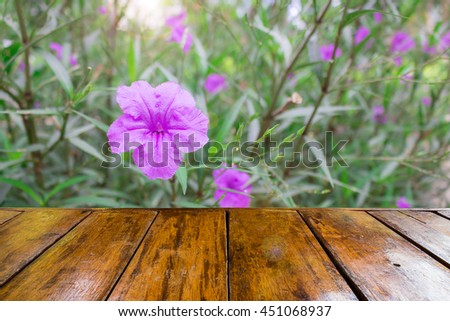 empty wooden table and pink ruellias ,wild petunias