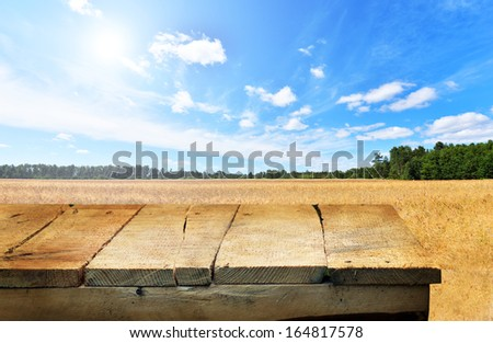 empty wooden table and summer field in background. Great for product display montages. - stock photo