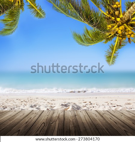 Empty wooden table. Coconut palm trees, sandy beach, ocean and perfect sky. Tropical background. - stock photo