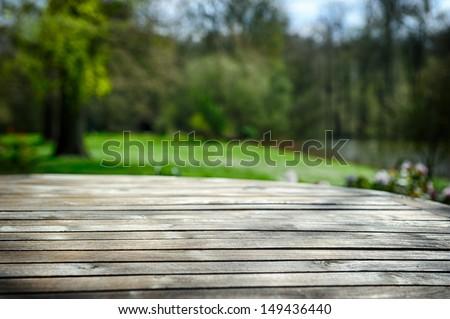 Empty wooden table in green spring garden - stock photo