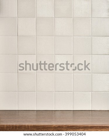Empty wooden table in the kitchen, tile white wall